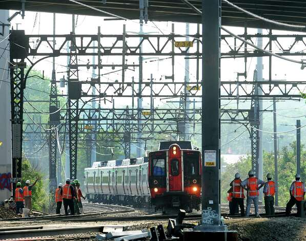 The first Metro-North train to rumble though the scene where two trains collided on Friday approaches the Interstate 95 overpass at the Bridgeport/Fairfield border on Tuesday, May 21, 2013. Photo: Cathy Zuraw / Connecticut Post