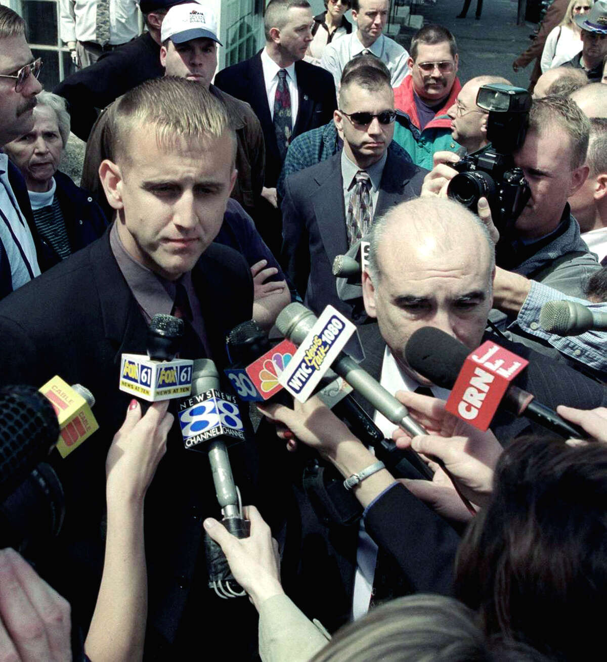 Then New Milford police officer Scott Smith, left, and his attorney, John Kelly, are grilled by the media outside the Litchfield courthouse on May 11, 2000 after his sentencing in the Dec. 29, 1998 shooting of Franklyn Reid. Among the trhong are off-duty New Milford police officers who went to Litchfield to support Officer Smith. Spectrum file photo