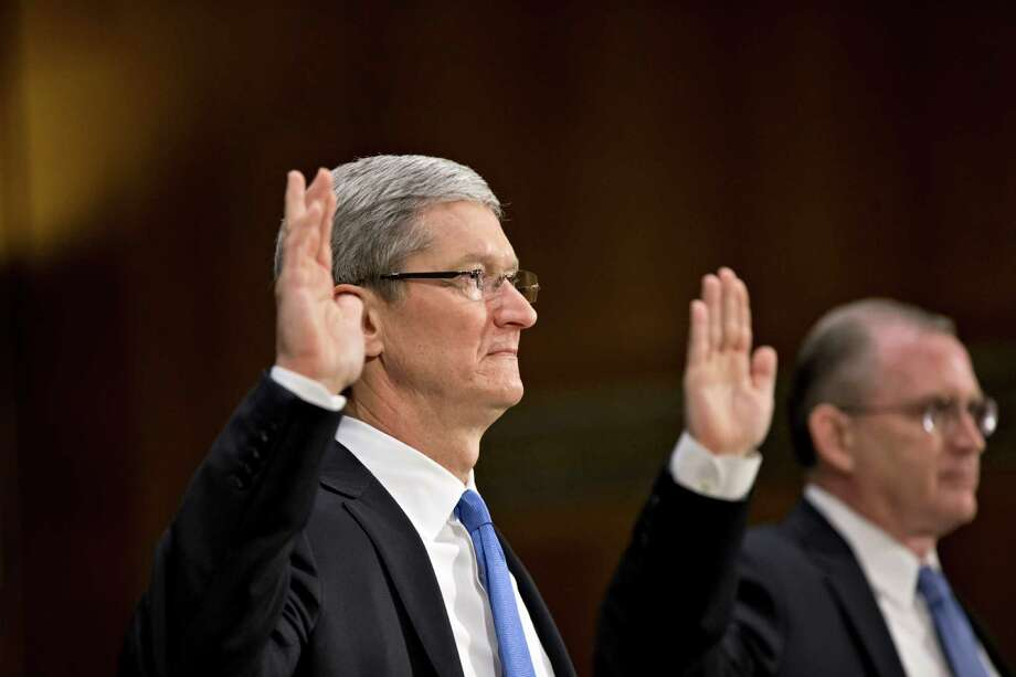 Apple CEO Tim Cook, left, and Phillip A. Bullock, right, Apple's head of Tax Operations, are sworn in on Capitol Hill in Washington, Tuesday, May 21, 2013, prior to testifying before the Senate Homeland Security and Governmental Affairs Permanent subcommittee on Investigations hearing to examine the methods employed by multinational corporations to shift profits offshore and how such activities are affected by the Internal Revenue Code. Lawmakers want to hear from Cook how Apple, the world's most valuable company, based in Cupertino, Calif., holds a billion dollars in an Irish subsidiary as a tax strategy, according to a report issued this week by the subcommittee.  (AP Photo/J. Scott Applewhite) Photo: J. Scott Applewhite