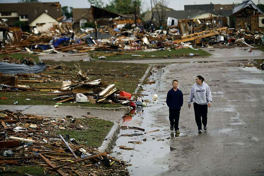 A woman and young boy walk along a street as they view destroyed house on May 21, 2013 in Moore, Oklahoma. Families returned to a blasted moonscape that had been an American suburb Tuesday after a monstrous tornado tore through the outskirts of Oklahoma City, killing at least 24 people. Nine children were among the dead and entire neighborhoods vanished, with often the foundations being the only thing left of what used to be houses and cars tossed like toys and heaped in big piles. Photo: Joshua Lott, AFP/Getty Images