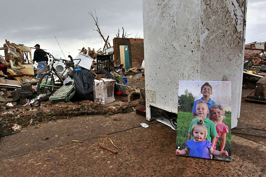 Rodney Heltcel, left, salvages the wreckage of his home for photos and irreplaceable items, such as the print of his grandchildren he placed at right, a day after a tornado moved through Moore, Okla., Tuesday, May 21, 2013. The huge tornado roared through the Oklahoma City suburb, flattening entire neighborhoods and destroying an elementary school with a direct blow as children and teachers huddled against winds. Photo: Brennan Linsley, Associated Press