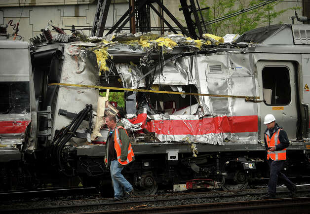 Metro North train cars heavily damaged in Friday's derailment are pulled from the scene after being hoisted back on to the tracks in Bridgeport. Conn. on Sunday, May 19, 2013. Photo: Brian A. Pounds / Connecticut Post