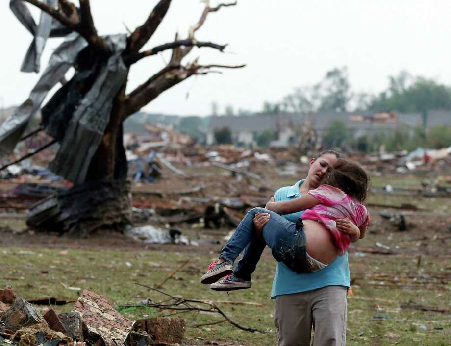 A woman carries a child through a field Monday near the collapsed Plaza Towers Elementary School in Moore, Okla. Photo: Sue Ogrocki, STF / AP