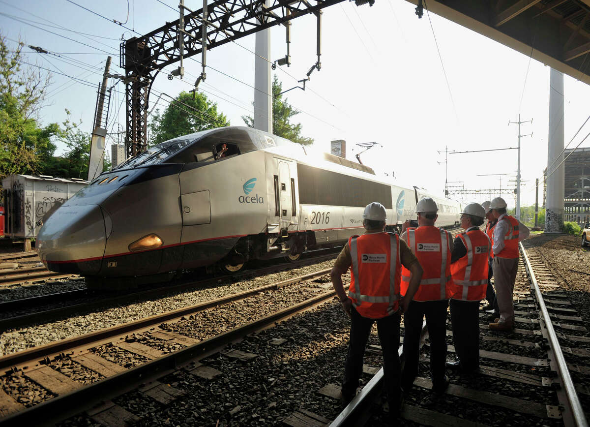 An Acela train operator waves to officials surveying the scene in Bridgeport on Tuesday, May 21, 2013, where a Metro-North train derailed the week before. On Tuesday, limited service between Grand Central and New Haven opened up. Officials plan to have a normal full-service schedule on Wednesday.