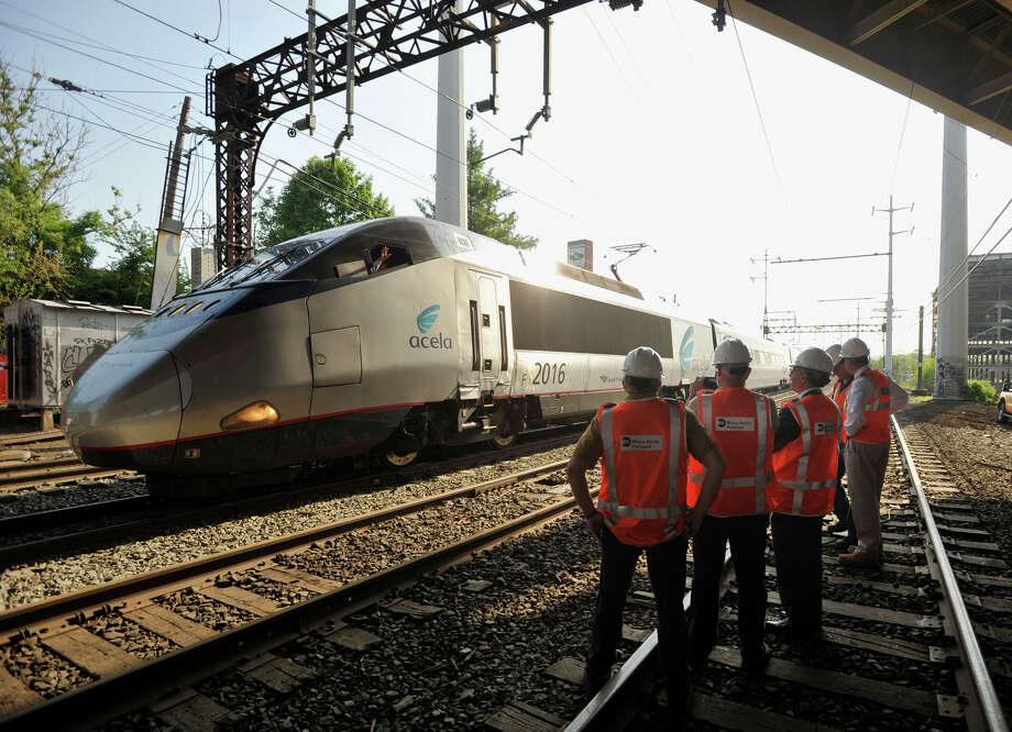 An Acela train operator waves to officials surveying the scene in Bridgeport on Tuesday, May 21, 2013, where a Metro-North train derailed the week before. On Tuesday, limited service between Grand Central and New Haven opened up. Officials plan to have a normal full-service schedule on Wednesday. Photo: Jason Rearick / Stamford Advocate