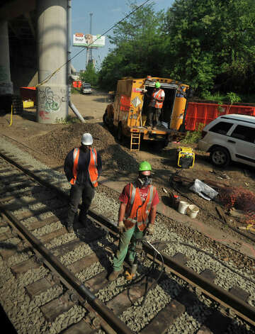 Rail workers tend to the tracks on Tuesday, May 21, 2013 where a Metro-North train derailed in Bridgeport. On Tuesday, limited service between Grand Central and New Haven opened up. Officials plan to have a normal full-service schedule on Wednesday. Photo: Jason Rearick / Stamford Advocate