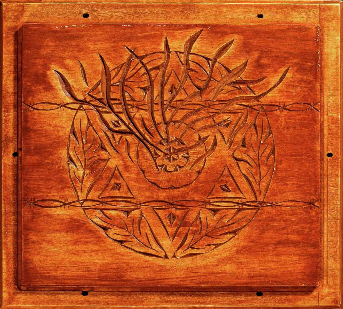 A collection of wood chip carvings by Harvey Paris is on exhibit at the Easton Public Library through June 30. Above the Star of David is overwhelmed by fire and barbed wire.