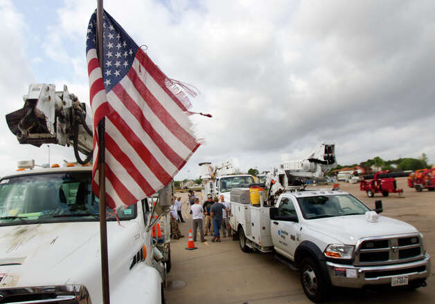 An American Flag flies as a CenterPoint Energy crew prepares to leave for Oklahoma, Tuesday, May 21, 2013, in Houston. The 60-employee entourage is going to help restore power to those effected by the tornado that happened Monday. Photo: Cody Duty, Houston Chronicle / © 2013 Houston Chronicle