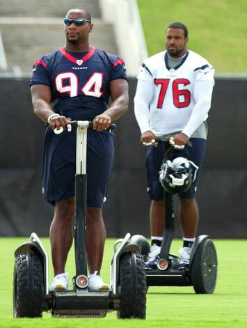 Houston Texans Antonio Smith (94) and Duane Brown (76) arrive at the practice field aboard Segways during Texans' Organized Team Activities at the Methodist Training Center Tuesday, May 21, 2013, in Houston. Photo: Brett Coomer, Houston Chronicle / © 2013 Houston Chronicle