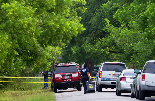 Police investigate the scene after a body was found burned in a car in the 10500 block of Exeter, Tuesday, May 21, 2013, in Houston. Photo: Cody Duty, Houston Chronicle / © 2013 Houston Chronicle
