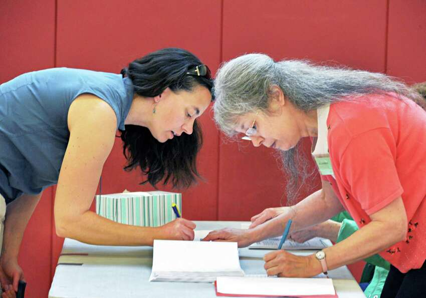 Voter Karen Davis, left, signs in with election inspector Jill Harbeck at Eagle Point Elementary sch