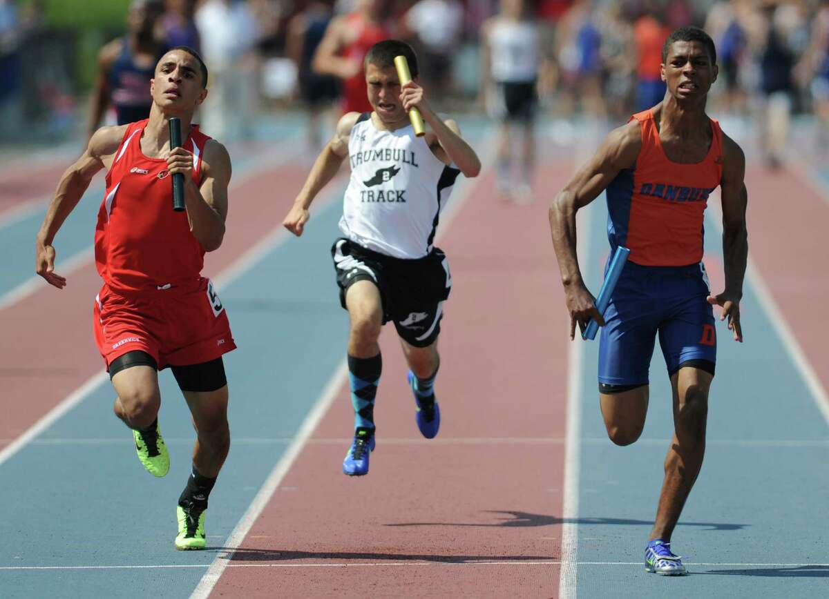 Danbury's Mathew Andrew, right, edges out Greenwich's Austin Longi, left, and Trumbull's Joe Matera, in the final leg of the boys 4x100 meter relay race at the FCIAC Track and Field Championships at Danbury High School in Danbury, Conn. on Tuesday, May 21, 2013. Danbury won the race.