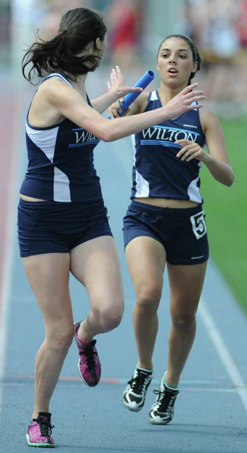 Wilton's Annika Sheehan, right, hands off to Alex Fiesel in the girls 4x800 meter relay at the FCIAC Track and Field Championships at Danbury High School in Danbury, Conn. on Tuesday, May 21, 2013.  Wilton won the race, edging out Ridgefield. Photo: Tyler Sizemore / The News-Times