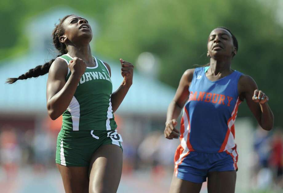 Norwalk's Crystle Hill, left, celebrates after beating Danbury's Niema Riley in the girls 100 meter dash final at the FCIAC Track and Field Championships at Danbury High School in Danbury, Conn. on Tuesday, May 21, 2013. Photo: Tyler Sizemore / The News-Times