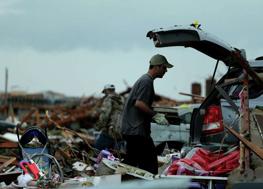 Justin Stehan salvages photographs from his tornado-ravaged home Tuesday, May 21, 2013, in Moore, Okla. A huge tornado roared through the Oklahoma City suburb Monday, flattening entire neighborhoods and destroying an elementary school with a direct blow as children and teachers huddled against winds. (AP Photo/Charlie Riedel) Photo: Charlie Riedel