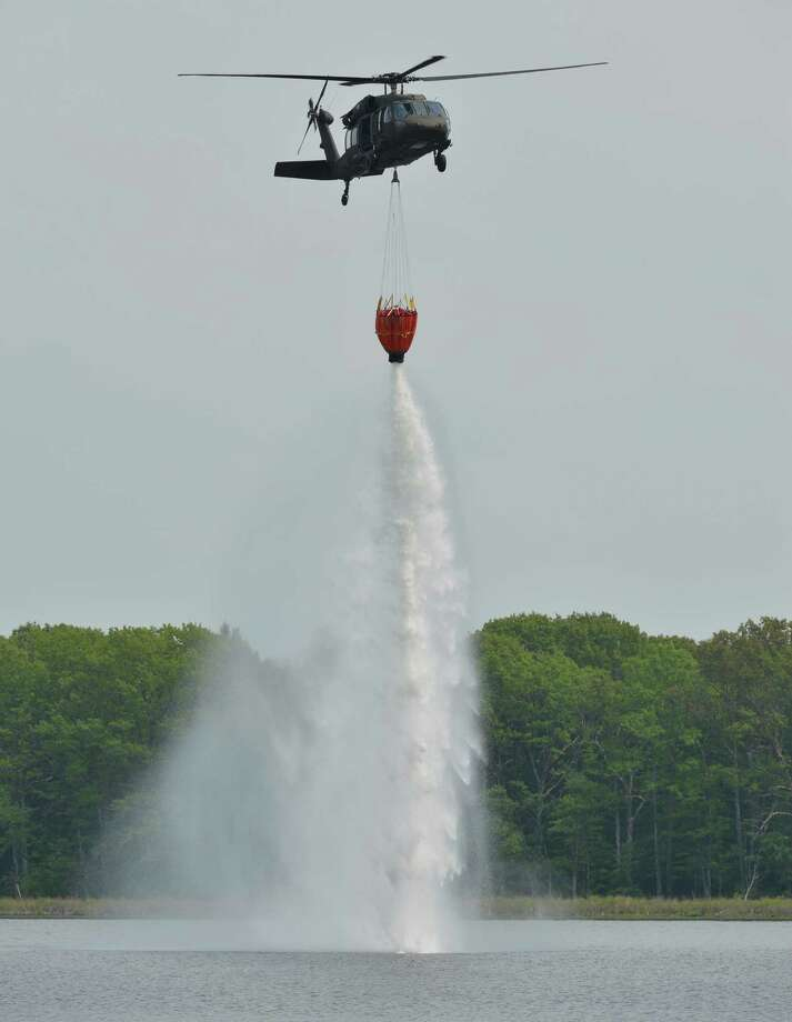 A Army National Guard helicopter drops water from a special basket attached to the underside of a Blackhawk helicopter May 21, 2013, during water drop exercises on Round Lake in Saratoga County, N.Y.   The guardsman are practicing to assist firefighters if they were deployed to a forest fire.   (Skip Dickstein/Times Union) Photo: SKIP DICKSTEIN / 00022513A
