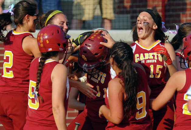 St. Joseph players surround teammate Jenn Vazquez as she comes in to home plate with a home run, during FCIAC Softball Championship semi-final action against Darien at Sacred Heart University in Fairfield, Conn. on Tuesday May 21, 2013. Photo: Christian Abraham / Connecticut Post