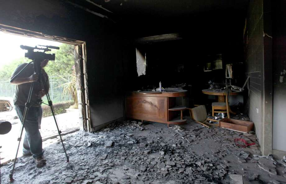 FILE - This Sept. 13, 2012 file photo shows a cameraman filming one of  U.S. consulate burnt out offices after an attack that killed four Americans, including Ambassador Chris Stevens on the night of Tuesday, Sept. 11, 2012, in Benghazi, Libya. The U.S. has identified five men they believe might be behind the attack on the diplomatic mission in Benghazi, Libya, last year, and have enough evidence to justify seizing them by military force as suspected terrorists _ but not enough proof to try them in a U.S. civilian criminal court, the process the Obama administration prefers, U.S. officials said. (AP photo/Mohammad Hannon, File) Photo: Mohammad Hannon