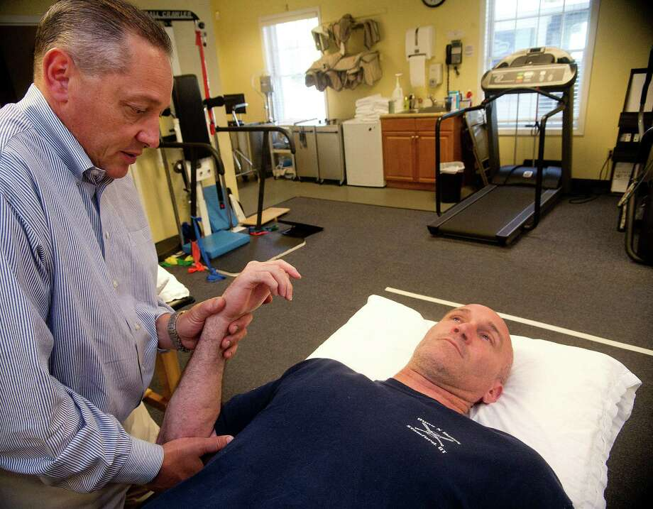 Troy Stauser works with Richard Preneta at Prenetta Physical Therapy in Fairfield, Conn., for a critical arm injury he sustained in the line of duty as a Stamford Police Officer when he engaged in a foot pursuit of a robbery suspect last year. Photo: Lindsay Perry / Stamford Advocate