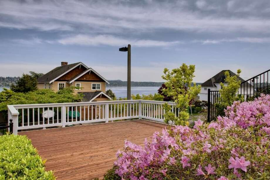 Deck of 1525 36th Ave. S. The 1,920-square-foot home, built in 1926, has three bedrooms, one bathroom, a rec room, a porch, a two-car garage and views of Lake Washington and Mount Rainier on a 6,900-square-foot lot. It's listed for $669,000. Photo: Courtesy Kathryn Hinds, Windermere Real Estate