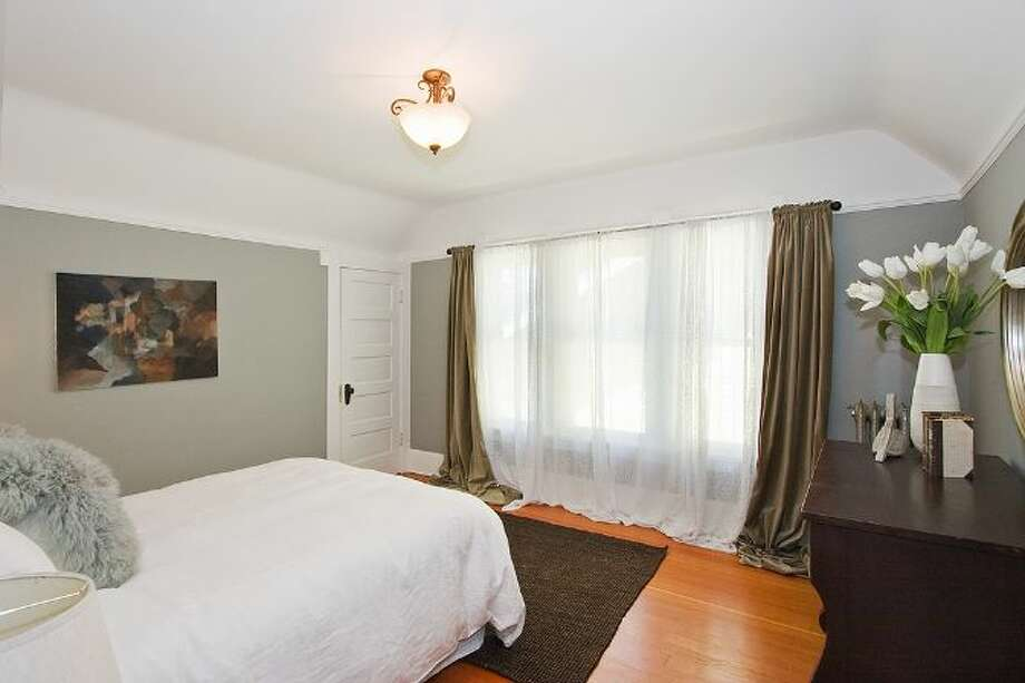 Bedroom of 2827 31st Ave. S. The 2,880-square-foot Craftsman, built in 1908, has five bedrooms and 2.75 bathrooms, including a basement apartment, box-beam ceilings and a patio on a 5,000-square-foot lot. It's listed for $699,888, although a sale is pending. Photo: Courtesy E.J. Gong, Windermere Real Estate