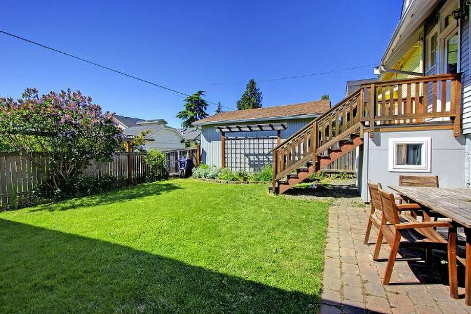 Yard of 2827 31st Ave. S. The 2,880-square-foot Craftsman, built in 1908, has five bedrooms and 2.75 bathrooms, including a basement apartment, box-beam ceilings and a patio on a 5,000-square-foot lot. It's listed for $699,888, although a sale is pending. Photo: Courtesy E.J. Gong, Windermere Real Estate