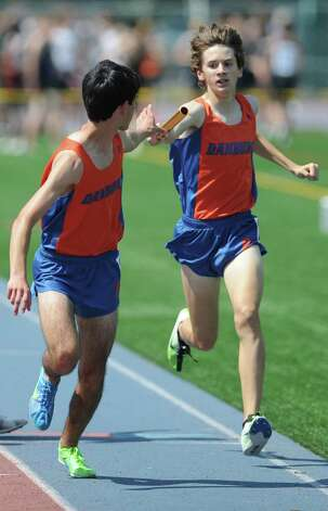 Danbury's Corey Mullins, right, hands off to Steven Farkas for the final leg of the boys 4x800 meter relay at the FCIAC Track and Field Championships at Danbury High School in Danbury, Conn. on Tuesday, May 21, 2013.  Danbury won the race, with Staples and Ridgefield finishing second and third. Photo: Tyler Sizemore / The News-Times