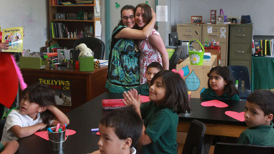 Teachers Oralia Lopez (left, background) and Sarah Powell embrace in a classroom after an announcement was made at Briscoe Elementary will receive a grant for sketchbook journals at all grade levels to enhance the curriculum. Photo: John Davenport / San Antonio Express-News