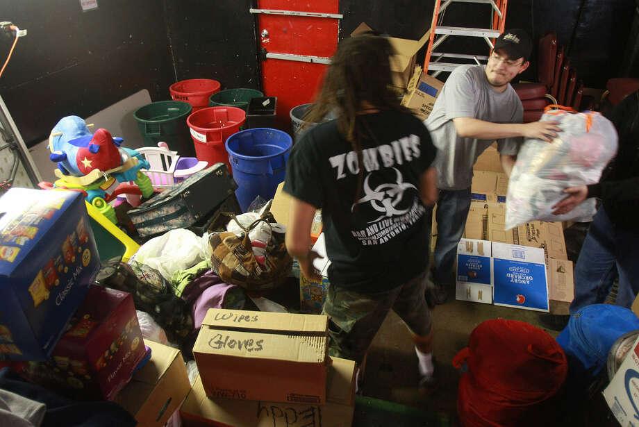 Joseph Carrasco (center) gets ready to hand off donated goods at Zombies nightclub on Thousand Oaks Drive. Photo: John Davenport / San Antonio Express-News