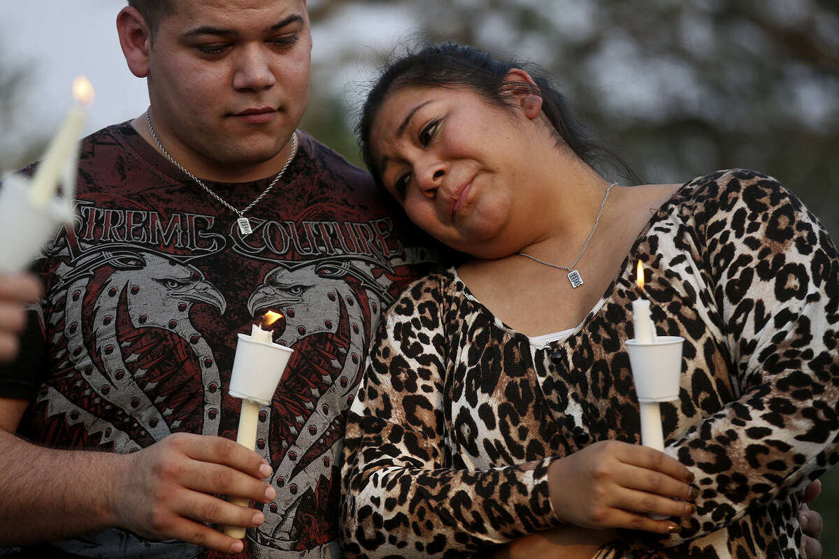 """Nadia Brackeen leans on her husband, Travis Brackeen, during the vigil for Plemmons, who is her cousin. """"We haven't lost him,"""" his father said. """"We've just misplaced him."""""""