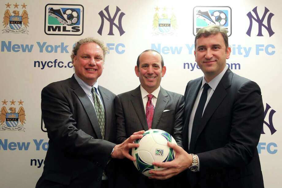 New York Yankees president Randy Levine, left, Major League Soccer Commissioner Don Garber, center, and Manchester City CEO Ferran Soriano pose for a photo at the MLS headquarter in New York, Tuesday, May 21, 2013.  The New York Yankees are partnering with Manchester City to own Major League Soccer's 20th team, which will be called New York City Football Club and plans to start play in the 2015 season. (AP Photo/Mary Altaffer) Photo: Mary Altaffer