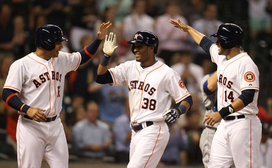 Astros right fielder Jimmy Paredes celebrates his three-run home run with Carlos Pena and J.D. Martinez.
