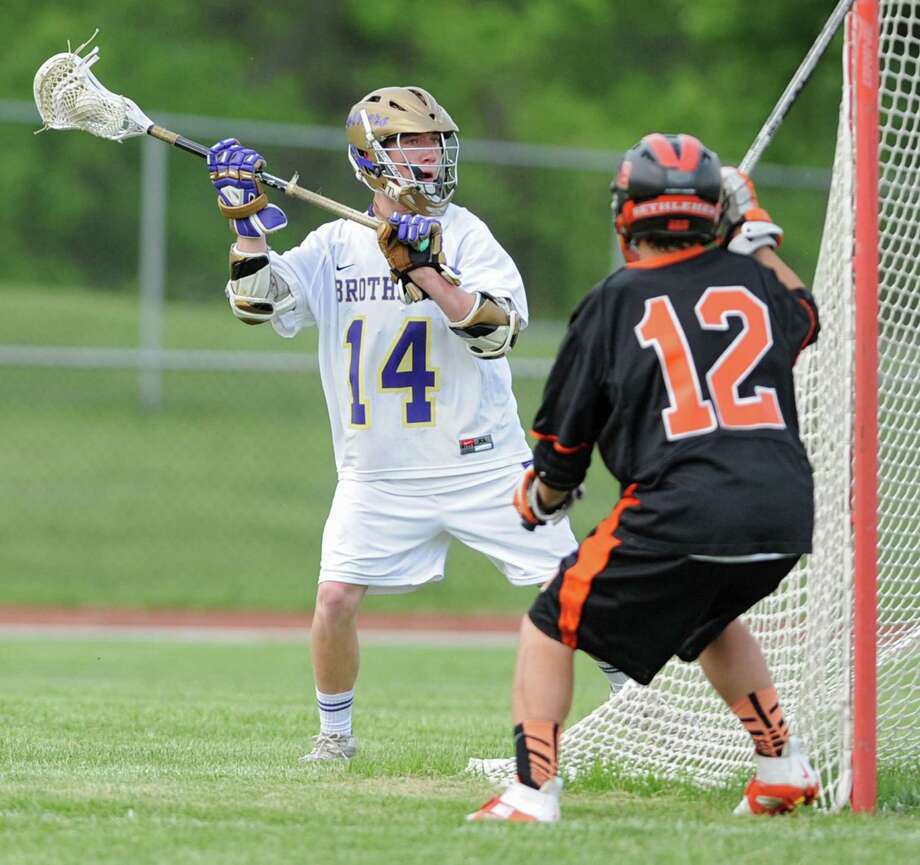 CBA attack John Bassett (#14) is defended by Bethlehem's Josh Fese near the net during the Section II Class A boys' lacrosse quarterfinal game at Christian Brothers Academy on Monday, May 21, 2013 in Albany, N.Y. (Lori Van Buren / Times Union) Photo: Lori Van Buren / 00022487A