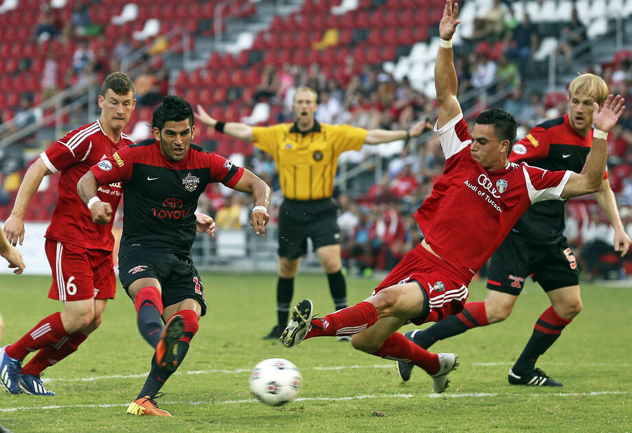 The Scorpions' Esteban Bayona (left) gets off a shot despite pressure from a diving Edgar Reyna of FC Tucson during U.S. Open Cup play Tuesday night at Toyota Field. Photo: Tom Reel / San Antonio Express-News
