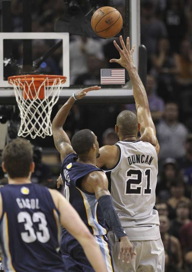 The Spurs' Tim Duncan (21) launches a shot against the Grizzlies' Mike Conley (11) in overtime of Game 2 of the 2013 Western Conference Finals at the AT&T Center on Tuesday, May 21, 2013. Spurs won 93-89 in overtime.