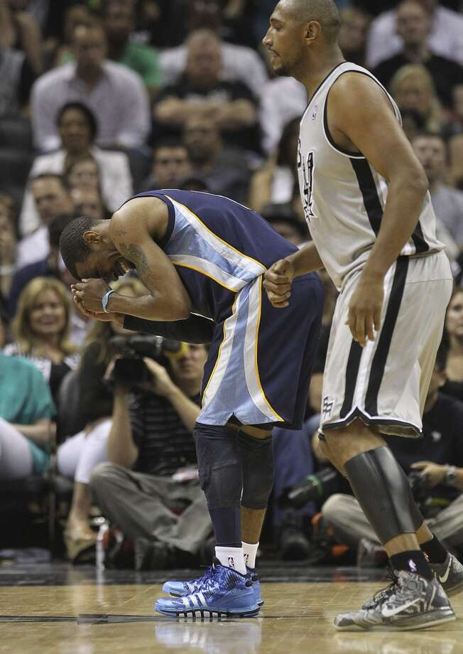 The Grizzlies' Mike Conley (11) bends over in apparent pain after being defended by the Spurs' Boris Diaw (33) in the second half of Game 2 of the 2013 Western Conference Finals at the AT&T Center on Tuesday, May 21, 2013. Spurs won 93-89 in overtime.