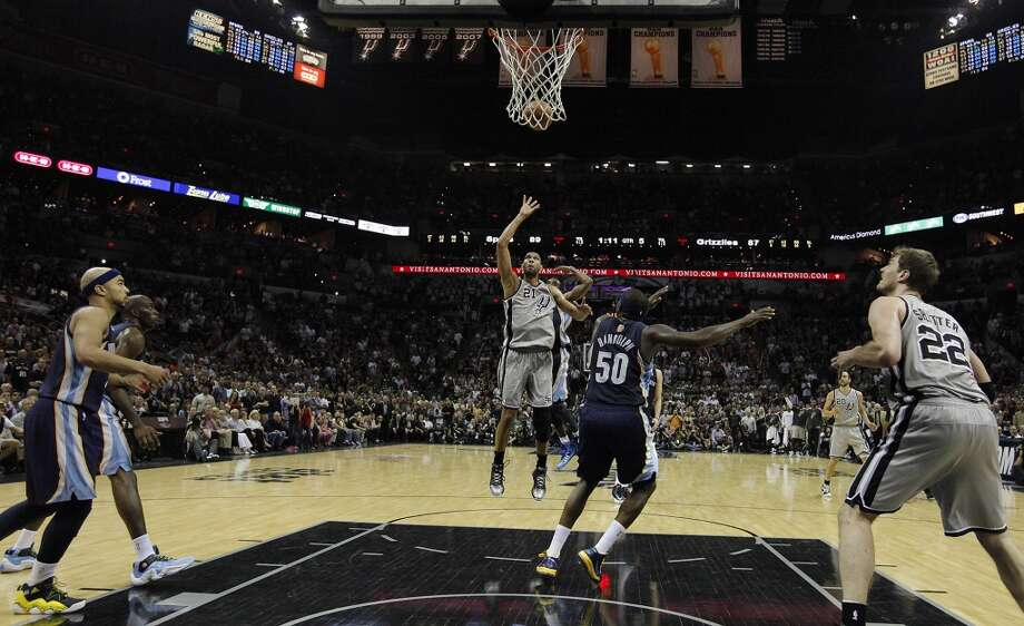 The Spurs' Tim Duncan (21) launches a shot against Memphis Grizzlies' Zach Randolph (50) in overtime of Game 2 of the 2013 Western Conference Finals at the AT&T Center on Tuesday, May 21, 2013. Spurs won 93-89 in overtime.