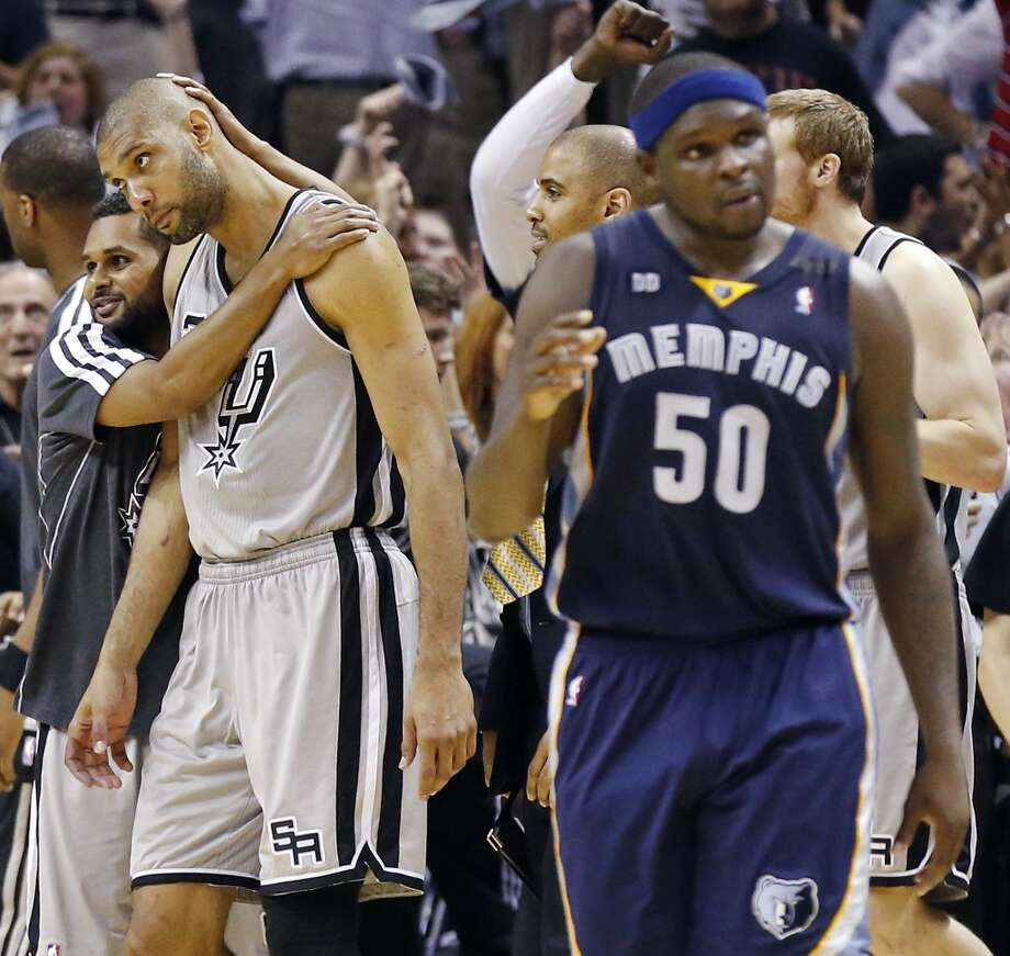 The Spurs' Patty Mills hugs Tim Duncan after Game 2 of the 2013 Western Conference finals as the Grizzlies' Zach Randolph walks off the court Tuesday, May 21, 2013 at the AT&T Center. The Spurs won 93-89 in overtime.