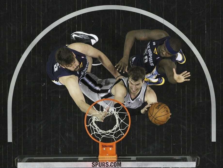 The Spurs' Tiago Splitter (22) goes up for a shot between the Grizzlies' Marc Gasol (33) and Zach Randolph (50) in Game 2 of the 2013 Western Conference Finals at the AT&T Center on Tuesday, May 21, 2013. Spurs won 93-89 in overtime.