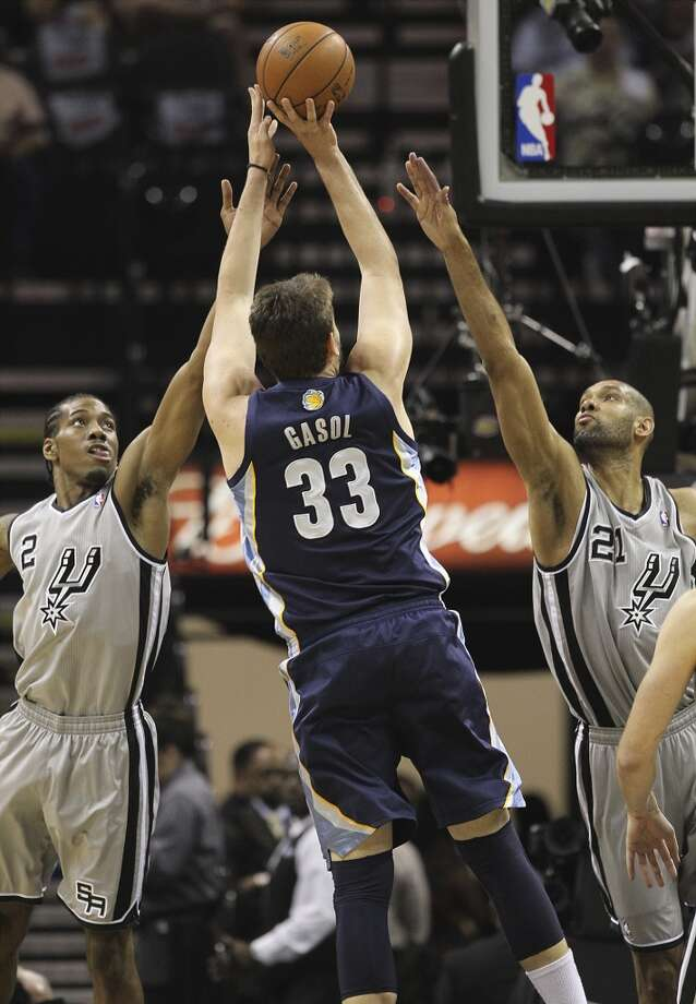 The Spurs' Kawhi Leonard (2) and Tim Duncan (21) reach to attempt a block against the Grizzlies' Marc Gasol (33) in the first half of Game 2 of the 2013 Western Conference Finals at the AT&T Center on Tuesday, May 21, 2013.