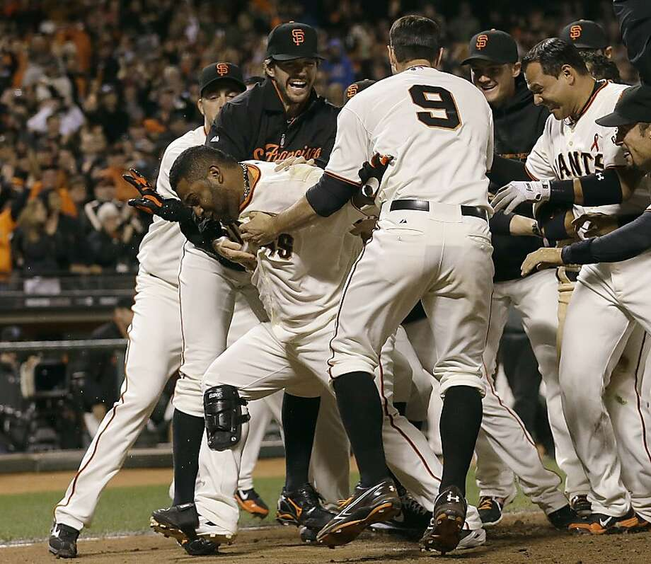 Pablo Sandoval (lower left) is mobbed after hitting a two-run walk-off homer in the 10th inning. The Giants had tied the game with two outs in the ninth. Photo: Jeff Chiu, Associated Press