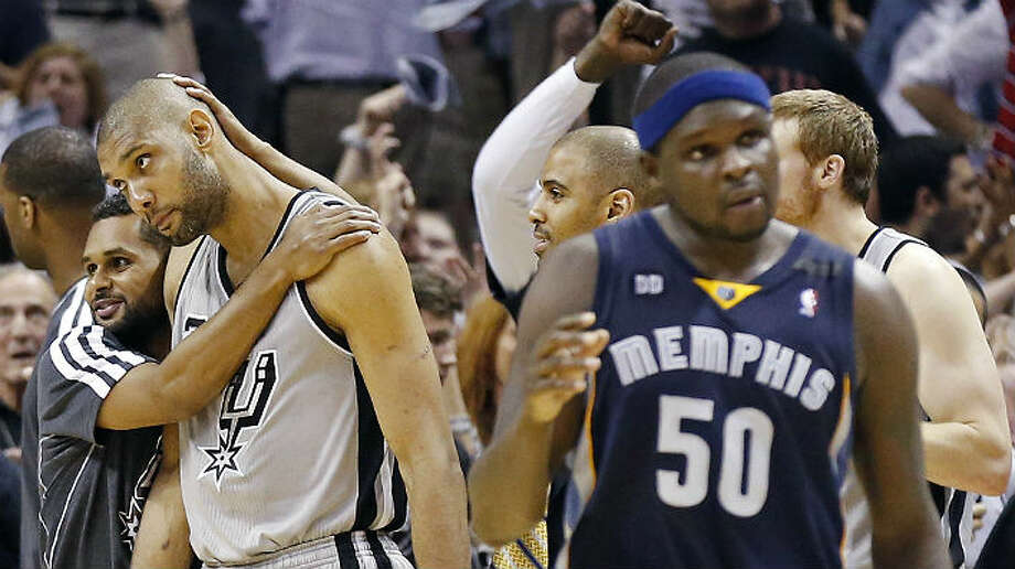 Tim Duncan gets a hug from Patty Mills after leading the Spurs to a 93-89 overtime victory in Game 2. Photo: Edward A. Ornelas, San Antonio Express-News