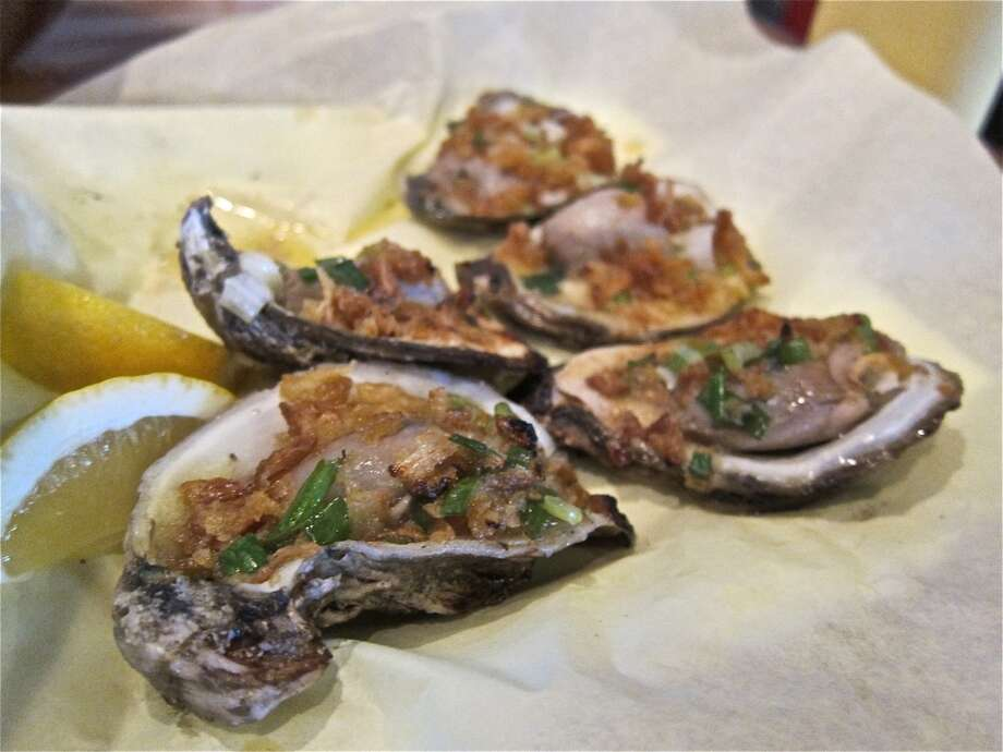 Grilled Oysters Vietnam, with butter, garlic and fried shallots, at Cajun Kitchen. Photo: Alison Cook, Houston Chronicle
