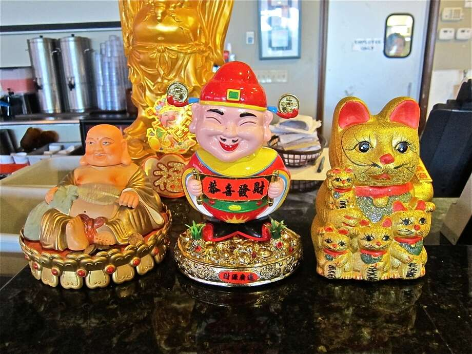 Moneycat, Confucian guy and Buddha figure all waving on a counter at Cajun Kitchen. Photo: Alison Cook, Houston Chronicle