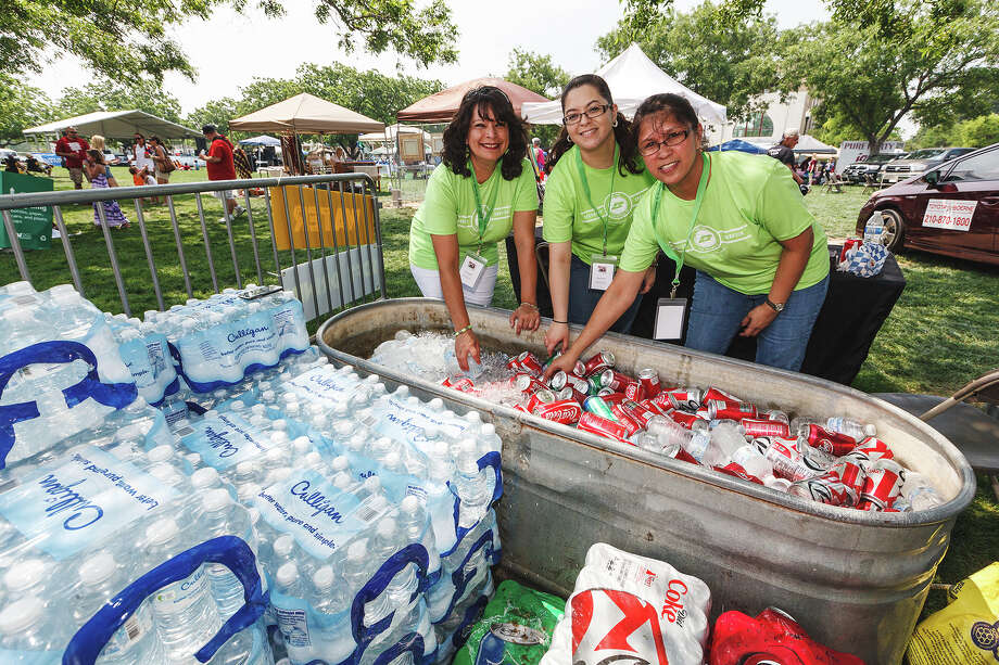 Gigi Aguilar (from left), Rosa Garza and Norie Jennings with Security Service Federal Credit Union work to supply the crowd with water and soft drinks as temperatures climb into the 90's during Best of BoerneFest 2013 at Main Plaza in Boerne on Saturday, May 18, 2013.  Photo by Marvin Pfeiffer / Prime Time Newspapers Photo: MARVIN PFEIFFER, Marvin Pfeiffer / Prime Time New / Prime Time Newspapers 2013