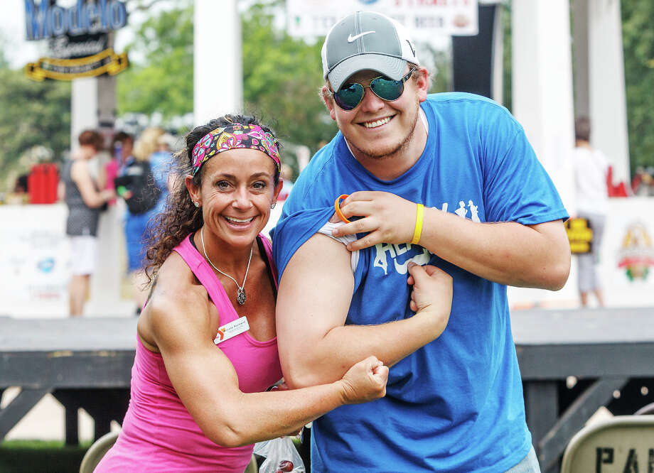 "Nicole Richard (left), fitness director of the Boerne YMCA, and Jacob Kerr, sports director of the organizan, playfully show off their ""guns"" during Best of BoerneFest at Main Plaza in Boerne on Saturday, May 18, 2013.  Photo by Marvin Pfeiffer / Prime Time Newspapers Photo: MARVIN PFEIFFER, Marvin Pfeiffer / Prime Time New / Prime Time Newspapers 2013"
