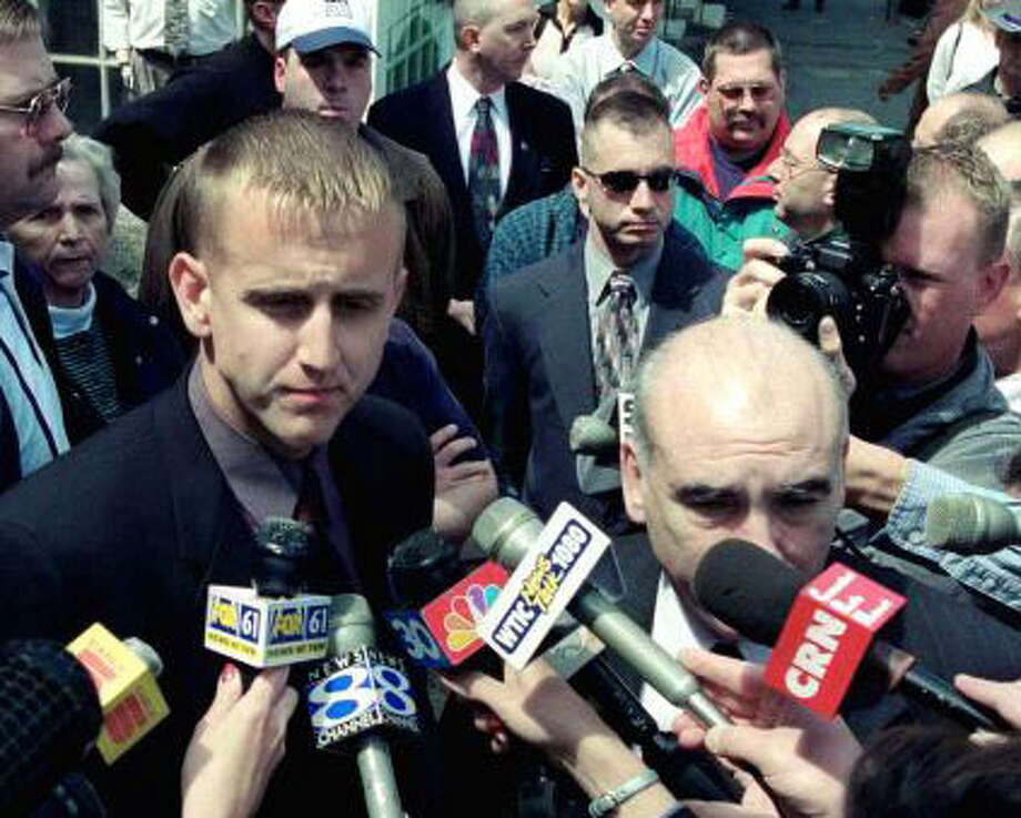 Then New Milford police officer Scott Smith, left, and his attorney, John Kelly, are grilled by the media outside the Litchfield courthouse, May 11, 2000, after his sentencing in the Dec. 29, 1998 shooting of Franklyn Reid. Among the throng are off-duty New Milford police officers who went to Litchfield to support Officer Smith. Photo: Contributed Photo