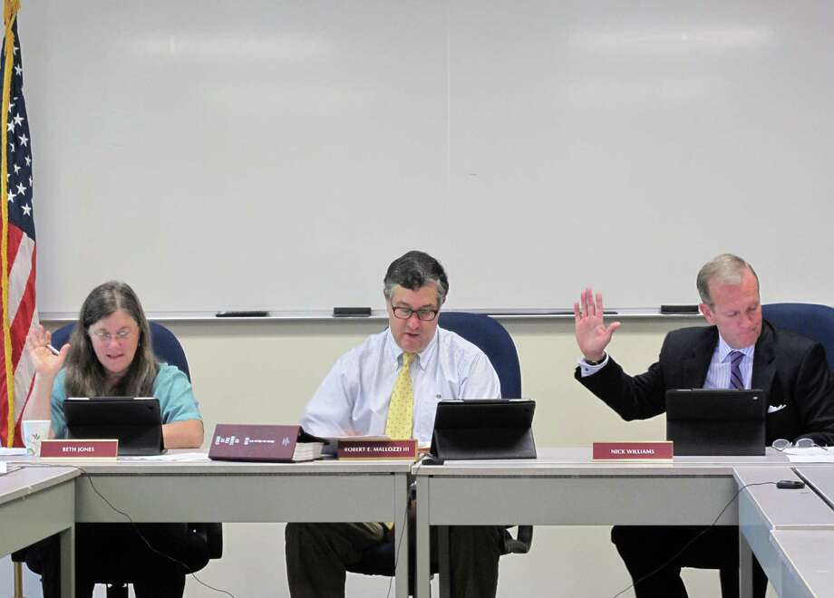 The New Canaan Board of Selectmen (from left: Beth Jones, Robert Mallozzi, Nick Williams) vote on an item during the May 21 BOS meeting. Photo: Tyler Woods