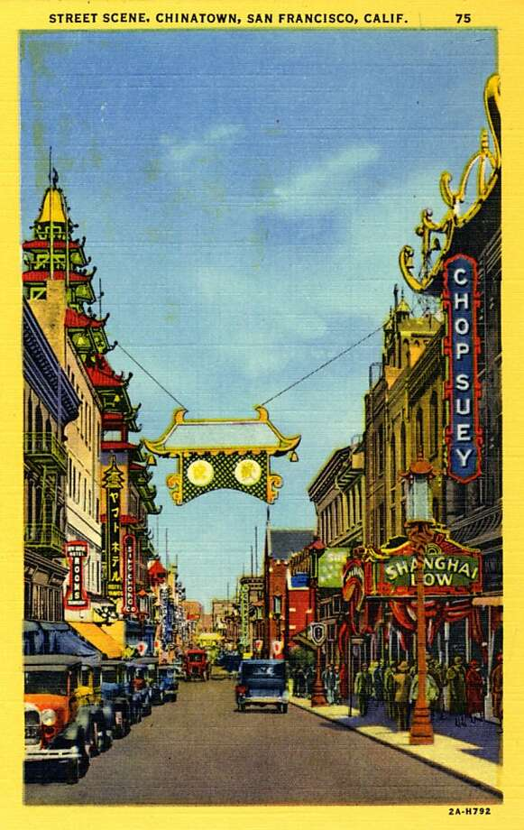 Vintage linen postcard showing a view down a street in Chinatown. Vintage automobiles line the street and pedestrians crowd the sidewalk. Store fronts with neon signs are visible down the street. Photo: Curt Teich Postcard Archives