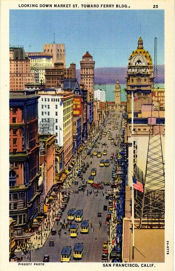 Vintage linen postcard showing a bird's eye view down Market Street towards the Bay.  The Street is teeming with cable cars, traffic and pedestrians and the Ferry Building is seen in the distance. Photo: Curt Teich Postcard Archives